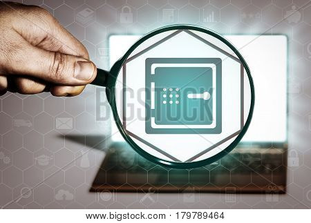 Hand holds the magnifying glass in front of an open notebook. Among the many icons attention is focused on the safe icon. Search for banks banking services finance protection.