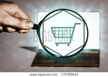 Hand holds the magnifying glass in front of an open notebook. Among the many icons attention is focused on the cart icon. Search for goods online shopping stores buy.