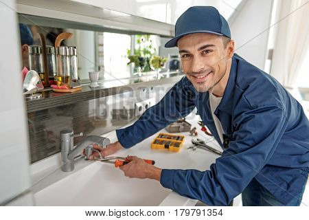 Interested plumber is repairing crane in kitchen. He looking at camera with smile. Portrait