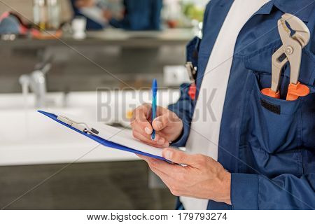 Repairman is holding clipboard with paper and pen. Close up of male hands and map-case