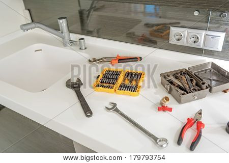 Different instruments are on countertop near sink with modern crane. close up