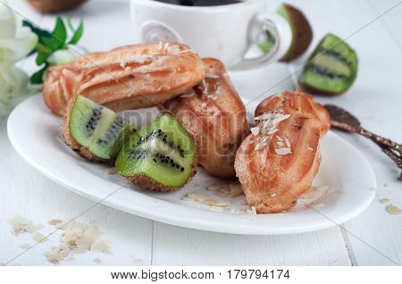 eclairs with cup of coffee and kiwi on a white wooden background.
