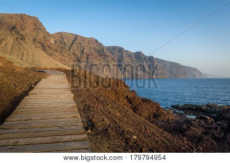 Wooden walking path at Punta de Tena. Los Gigantes rocks and ocean view at sunset light. Tenerife, Canarias, Spain.