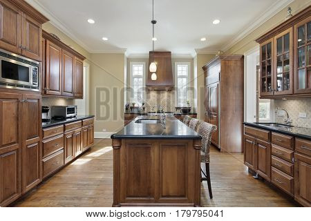 Kitchen in luxury home with black granite island top.