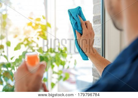 Careful male person is wiping glass with microfiber. He using detersive spray