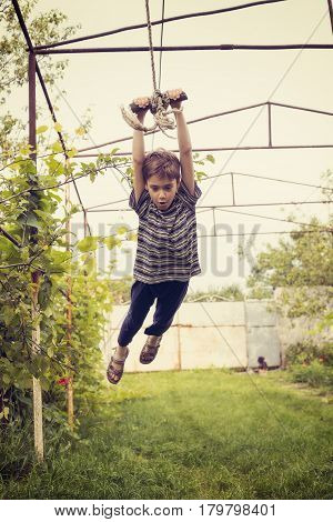 Cool boy swings on rope in the countryside enjoying process.