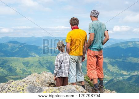 Friends Stand On A Rock Looking At The Mountain Landscape