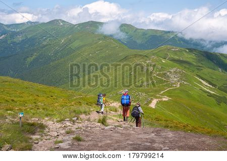 Travelers With Backpacks Are Walking Down The Ridge