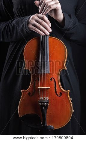 Violin music instrument of orchestra closeup with player hands on black