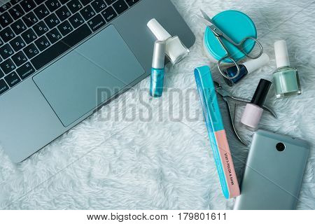 Set for manicure with laptop and smartphone on white fluffy background