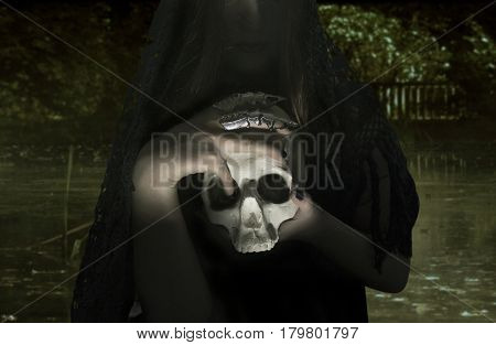 A witch woman holding a human skull on bog background photo.