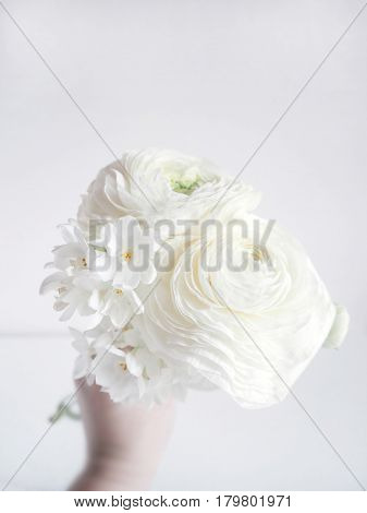 White wedding or birthday bouquet made of Persian buttercup, Ranunculus and daffodil, Narcissus, flowers, blurred background.