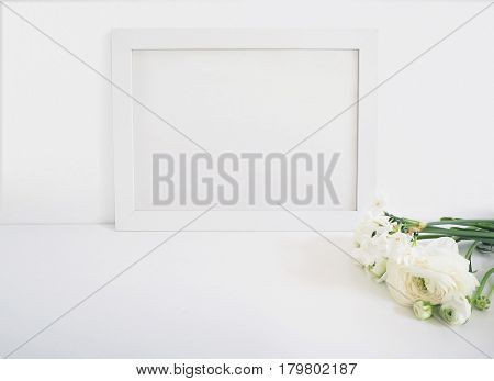 White blank wooden frame mockup with the Persian buttercup and daffodil flowers lying on the white table. Poster product design, styled stock feminine photography. Home decor.