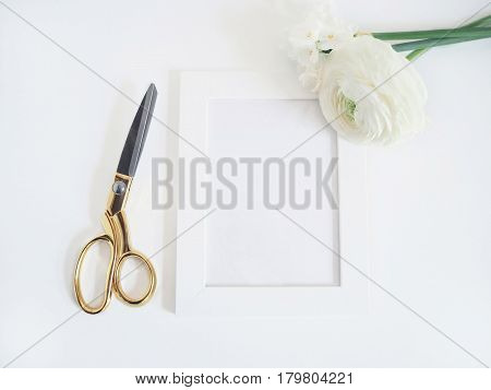 Styled stock photo. Feminine product mockup with bunch of buttercup, Ranunculus and daffodil flowers, blank white frame and golden scissors on white background, flat lay, top view.