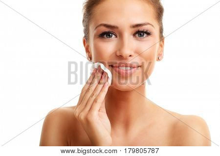 Portrait of adult woman smiling and using cotton pad against white background