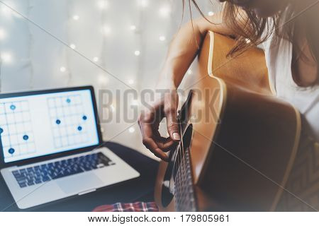 Hipster playing guitar in home atmosphere person studying on musical instrument notes in laptop on background glow bokeh Christmas illimination female hands in holiday on relax glitter decoration blur