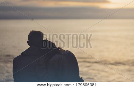 Couple hugging on the beach on background ocean sunrise silhouette two romantic people cuddling and looking on rear view evening seascape hipster enjoy sunset together travel holidays vacation