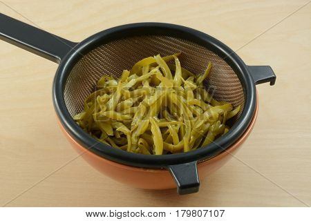 Canned French cut green beans draining in strainer