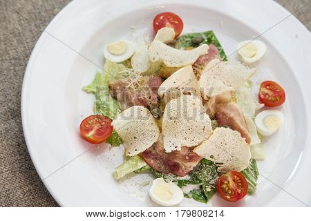 Caesar salad with croutons tomatoes bacon and chicken on a white plate