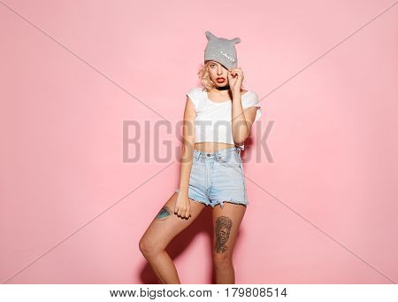 Young woman looking at camera touching her heading on the pink background.