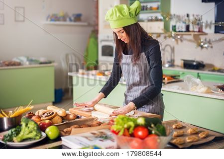 Young woman in casual clothes, apron and hat rolling dough for a pie in kitchen. Female baker making pastry.