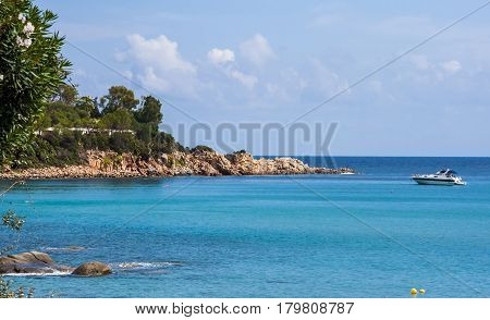 Scenery view on Italian island Sardinia sea shore beach rock coast and anchored boat in Arbatax sardegna