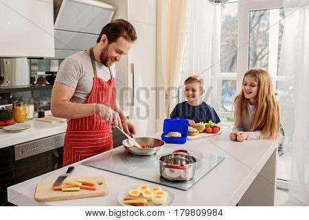 Joyful man is cooking for his children. He is standing in kitchen and smiling
