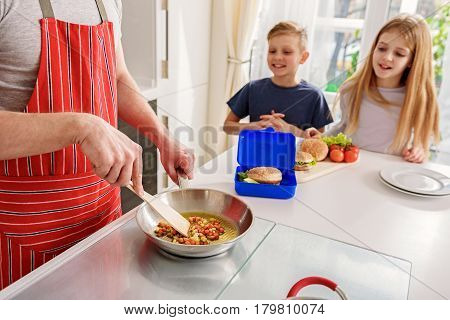 Hungry children are waiting for breakfast at home. They are sitting at table and smiling. Focus on father hands frying chopped vegetables on pan