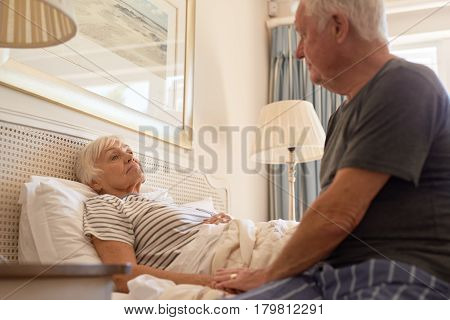 Sick senior woman being comforted by her caring and devoted husband while lying in bed at home in the morning