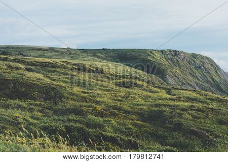 Sunset in the mountain natural landscape. Green valley on background dramatic sky clouds sea ocean. Panorama horizon perspective view of scenery hills Northern Spain alps. Travel mockup concept