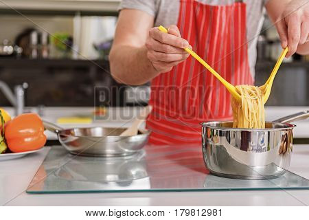 Close up of male hands taking noodle from pot on electric stove