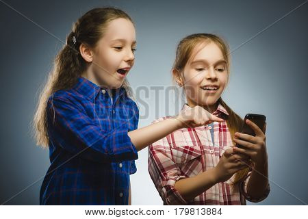 Two little happy girls using mobile or cell phone isolated grey background.