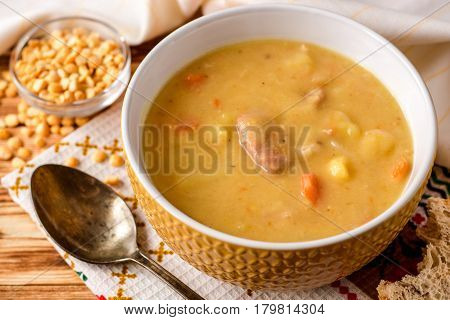 Split Pea Soup With Meat, Potatoes And Carrots In Ceramic Bowl On Wooden Background.