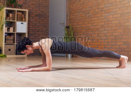 Thin young female yogi doing pilates plank pose on floor exercising at home.
