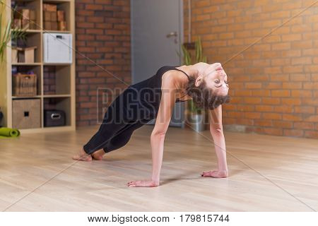 Woman doing yoga exercise standing in Table Top Pose Ardha Purvottanasana on floor at home.