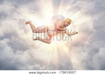 Funny overweight cupid aiming with the arrow of love with copy space