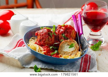 Turkey meat balls stuffed with feta cheese in tomato sauce.selective focus