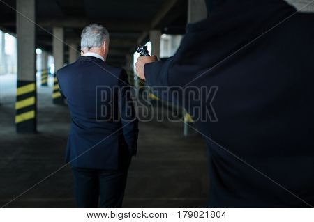 I will shoot. Angry strong dangerous criminal holding a handgun and aiming at the businessman while threatening him