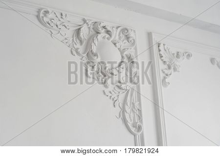 White wall molding with geometric shape and vanishing point. Luxury white wall design bas-relief with stucco mouldings roccoco element.
