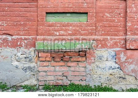 Close up obsolete partly demolished red brick wall with section painted green and grass growing next to it