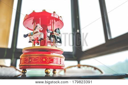 retro filtered toy music box red toned merry go round carousel horses