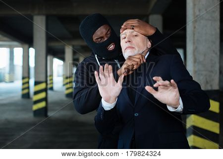 Committing a murder. Angry aggressive ruthless criminal holding a knife and holding a businessman while trying to kill him