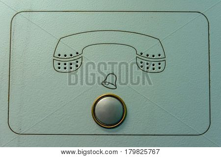 Close up old intercom with metal button and phone symbol on grey background