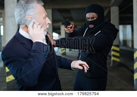 Daylight robbery. Serious handsome rich businessman speaking on the phone and turning around to the criminal while being robbed