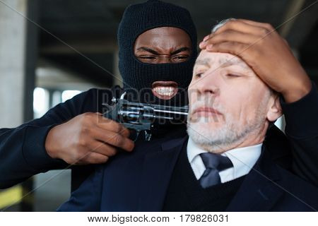 I need your money. Angry emotional male robber holding a businessman and threatening him with a gun while wanting his money