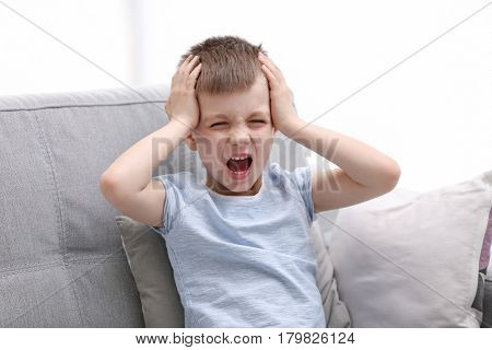 Little boy suffering from headache at home