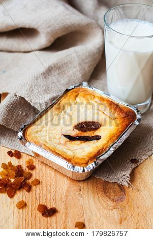 Sweet curd casserole with figs and raisins baked in the oven and milk in a glass on a wooden table. Cheesecake with figs and raisins in a baking dish for breakfast with a glass of milk.