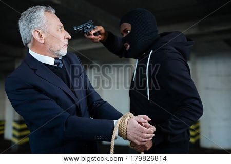 Give me money. Greedy strong male robber using a handgun and holding the rope while demanding money