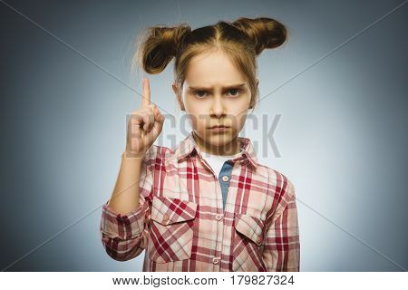 displeased and contemptuous girl with threatens finger isolated on gray background