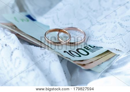 Wedding Cost Concept By Rings And Money And The Bride Dress In Background